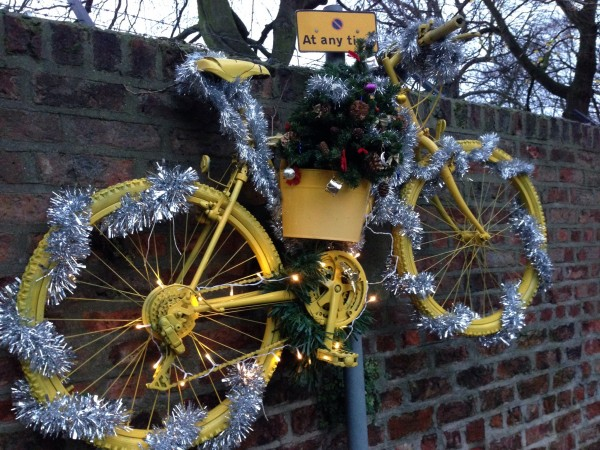 Tinsel decorating a Yellow Bicycle