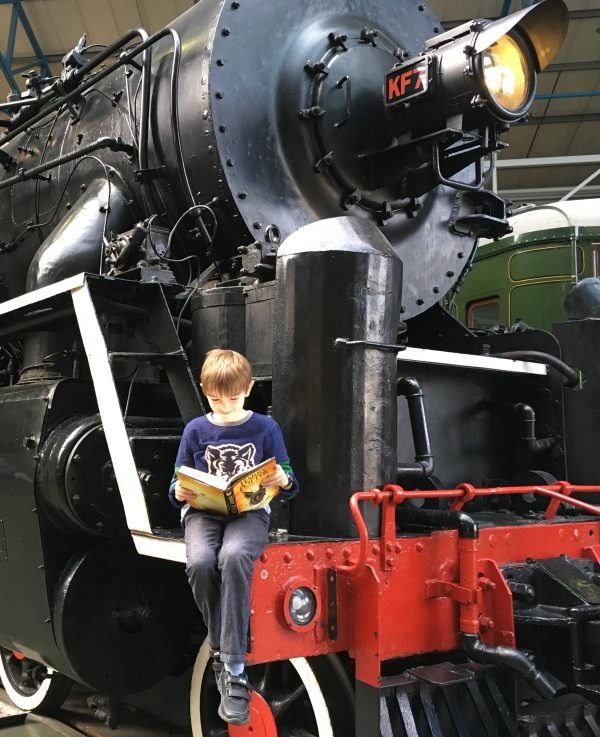 Alex reading as he sits on the front of the museum's largest locomotive