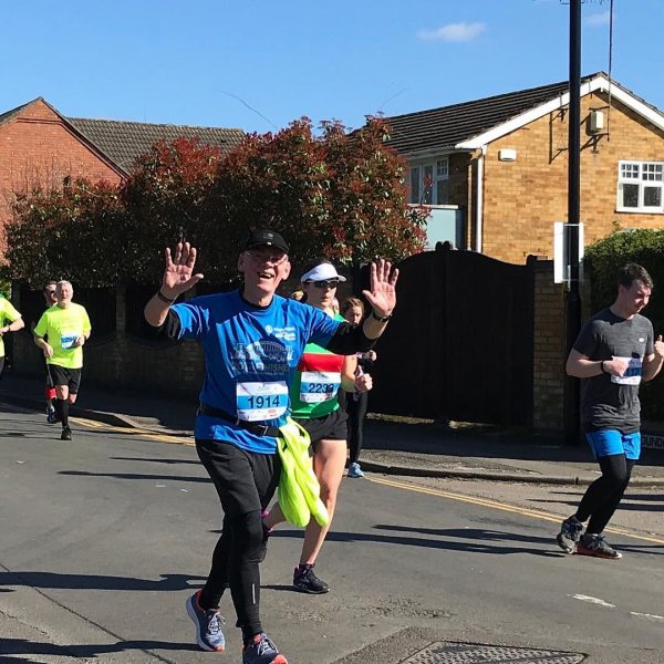 Barrie running the Coventry Half Marathon - arms raised aloft.
